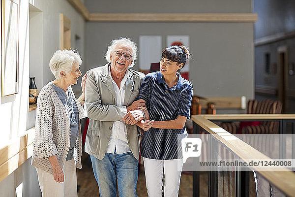 Gereatric nurse helping senior man and woman to walk down corridor