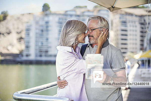 Senior couple taking a city break  holding map