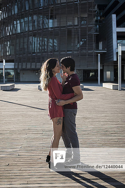 Affectionate young couple standing on city square