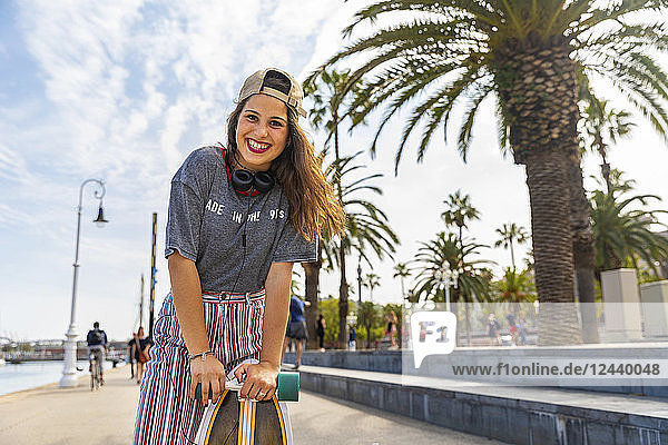 Portrait of happy teenage girl with skateboard on a promenade with palms