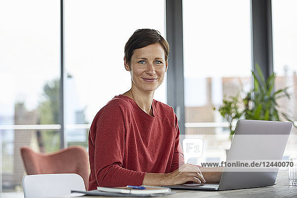 Portrait of smiling woman sitting at table at home using laptop
