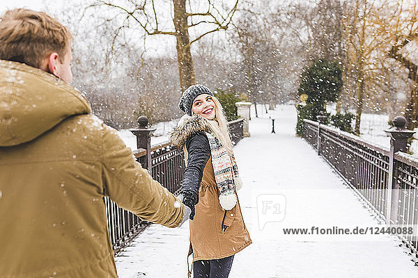 Portrait of happy teenage girl standing hand in hand with her boyfriend on footbridge on a snowy day