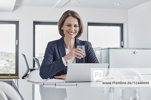 Portrait of smiling businesswoman using laptop at desk in office