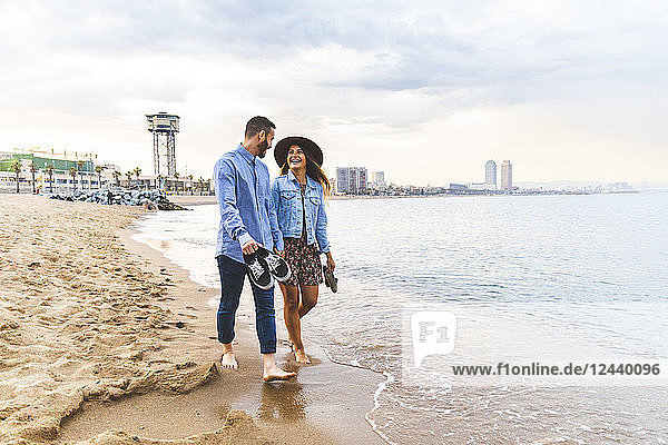 Spain  Barcelona  couple walking barefoot on the beach