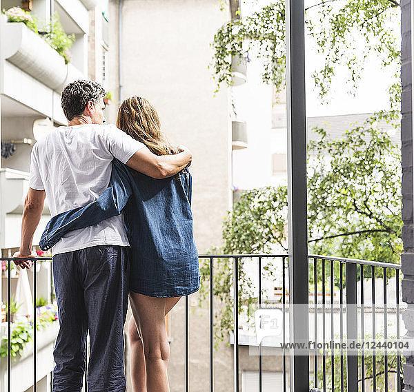 Rear view of couple in nightwear standing on balcony hugging