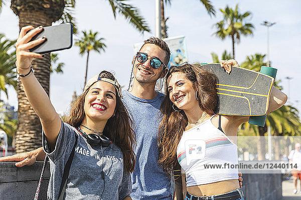 Three happy friends with skateboard taking a selfie