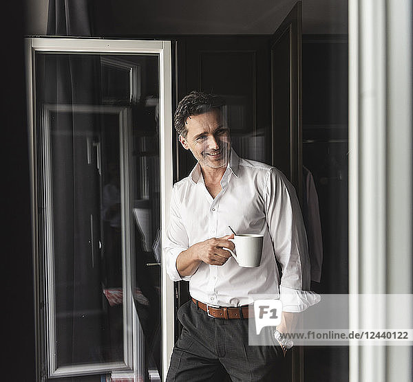 Smiling businessman with cup of coffee standing at the window at home