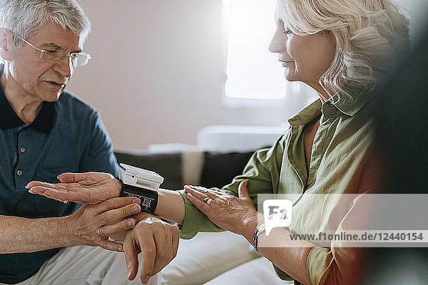 Senior couple taking blood pressure at home
