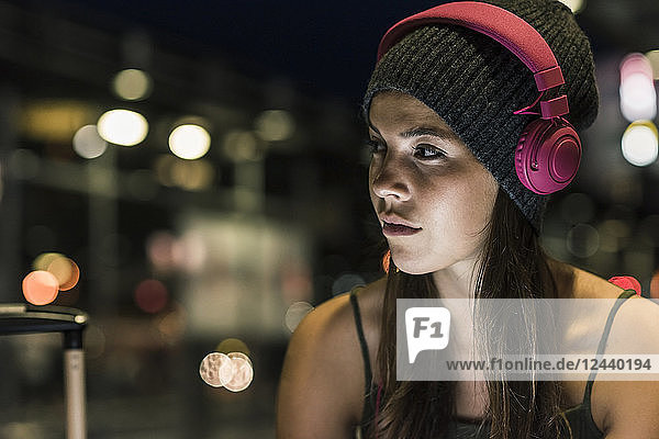 Portrait of young woman with headphones at night