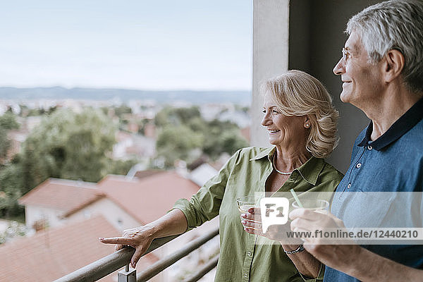 Smiling senior couple on balcony looking at view