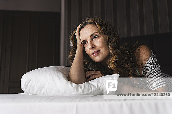 Thoughtful woman lying on bed at home looking away