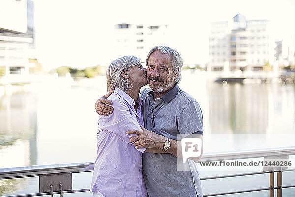 Senior couple taking a city break  kissing and embracing