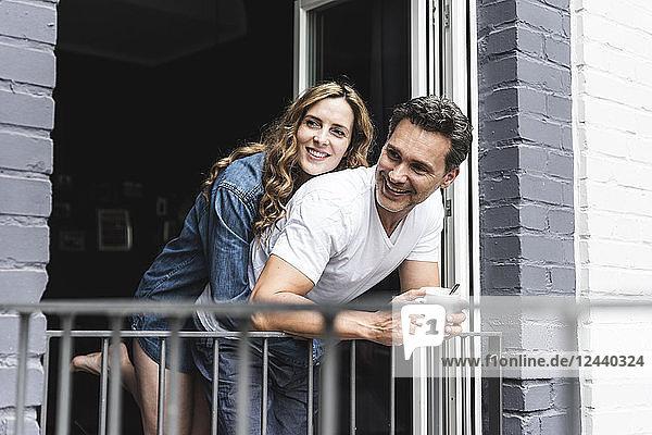 Happy couple in nightwear at home at balcony door
