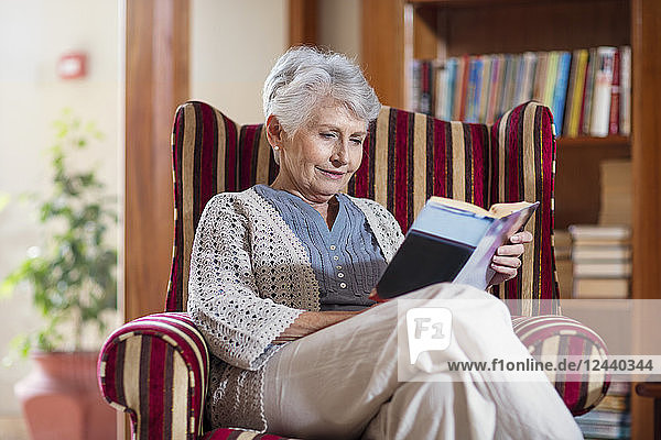 Senior woman siting in library  reading book
