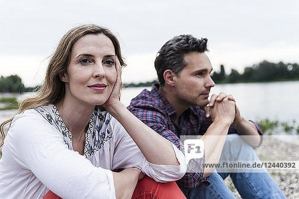 Couple sitting at the riverside thinking