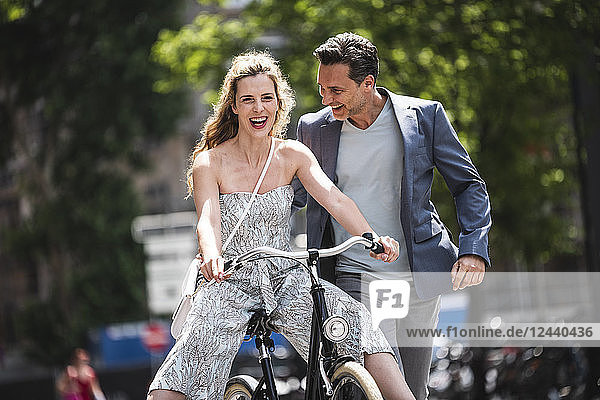 Happy carefree couple with bicycle in the city