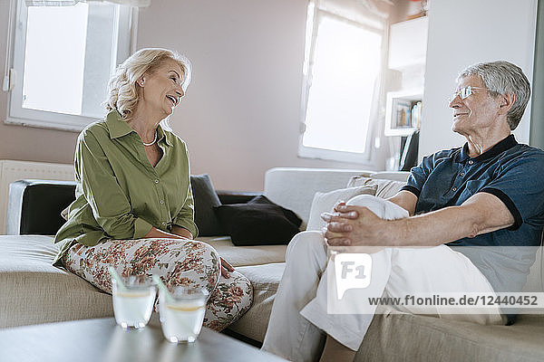 Senior couple at home talking on couch