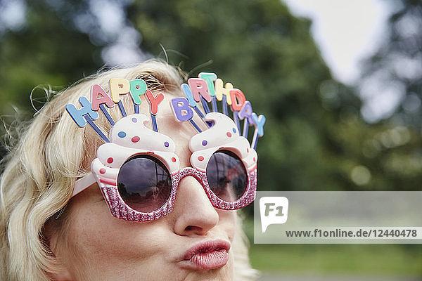 Woman pouting wearing birthday eyeglasses