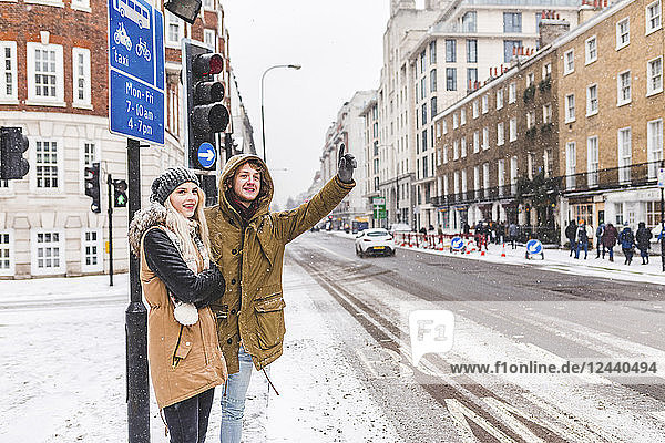 UK  London  young couple standing at roadside hailing taxi in winter