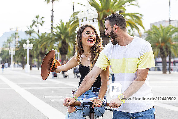 Spain  Barcelona  couple having fun and sharing a ride on a bike together on seaside promenade