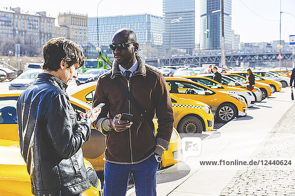 Russia  Moscow  two businessmen with smartphones in the city