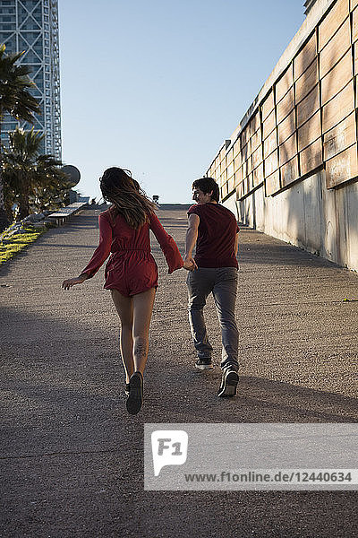 Spain  Barcelona  couple running hand in hand in the city