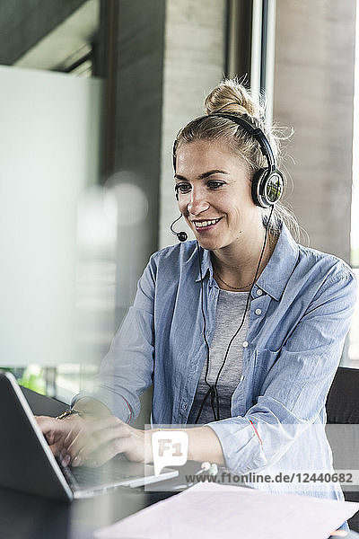 Young businesswoman sitting at desk  making a call  using headset and laptop