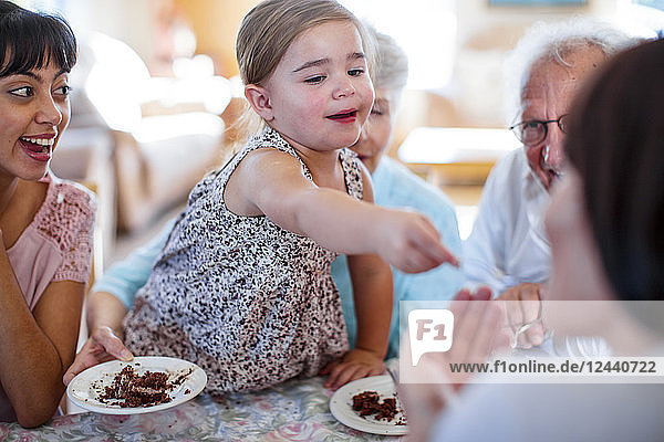 Grandparents celebrating a birthday with their granddaughter  eating chocolate cake