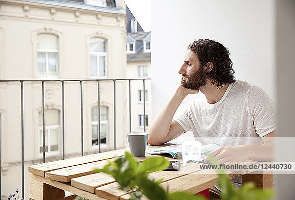 Daydreaming young man sitting with coffee mug and magazine on balcony looking at distance