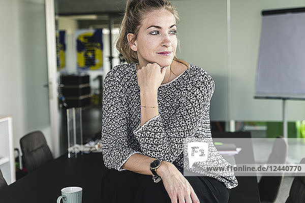 Young woman sitting in office  taking a break  daydreaming
