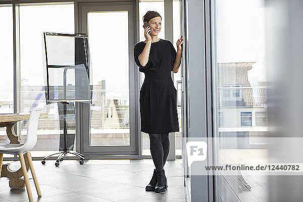 Smiling businesswoman in office on cell phone