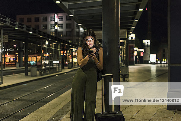 Young woman waiting at the station by night using cell phone