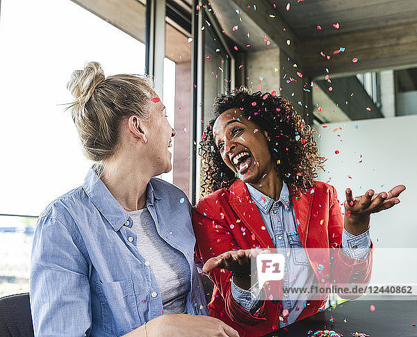 Young busniesswomen celebrating success  throwing confetti