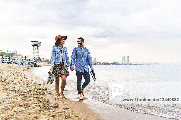 Spain  Barcelona  couple walking barefoot on the beach