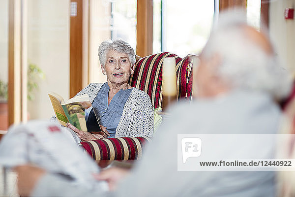 Senior man and woman sitting in library  reading book and newspaper