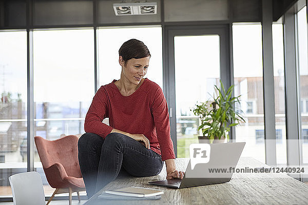 Smiling woman sitting on table at home using laptop