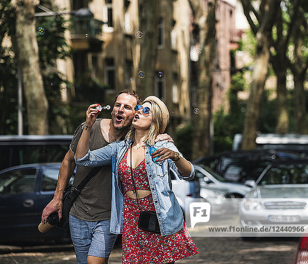 Couple blowing soap bubbles in the city together