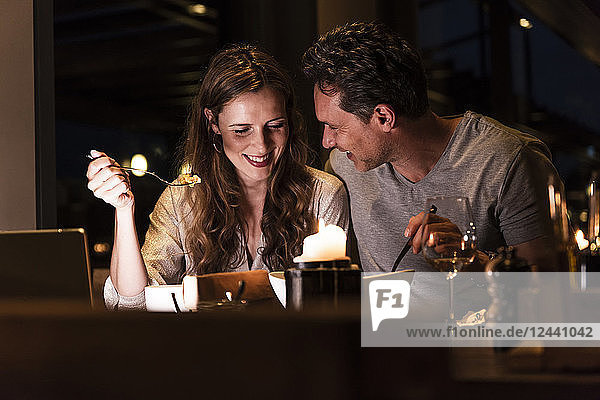 Smiling couple having dinner together