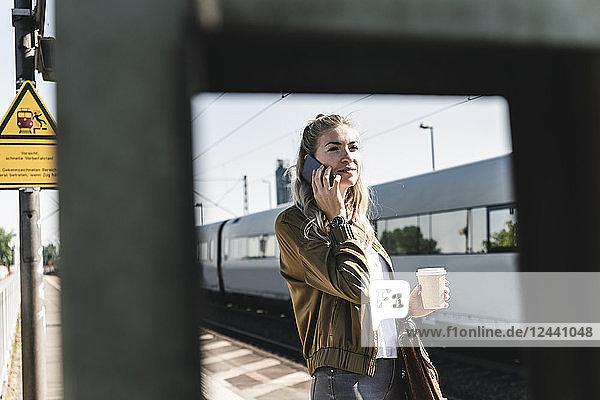 Young woman at train station talking at the phone