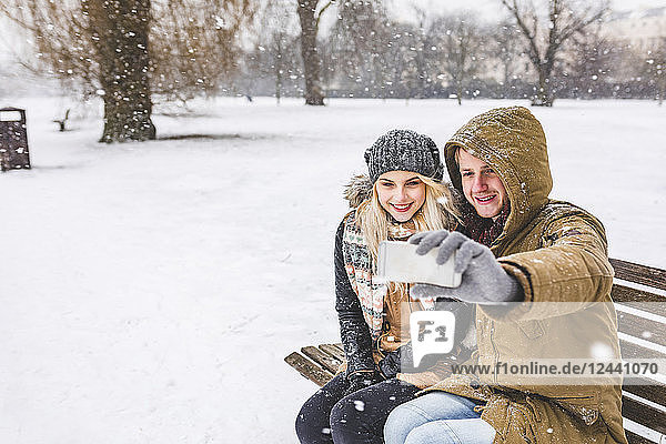 Happy young couple taking selfie with cell phone on snowy day in the park