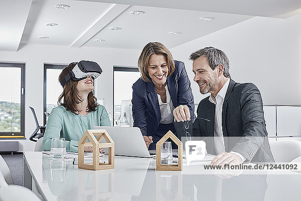 Business people having a meeting in office with VR glasses  laptop and architectural models