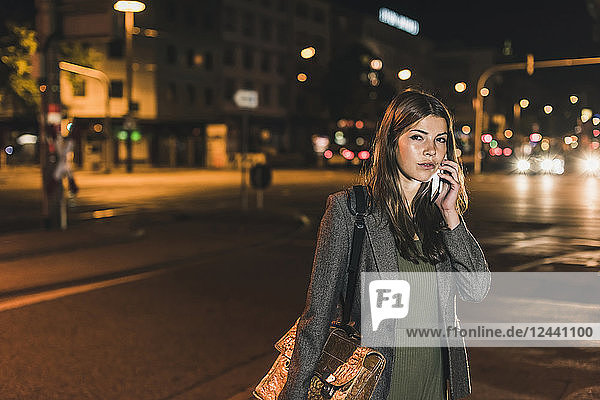 Portrait of young businesswoman with leather bag on the phone at night