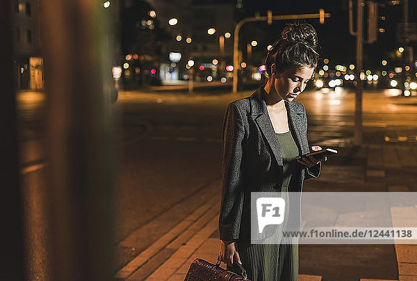 Young businesswoman with leather bag looking at cell phone by night