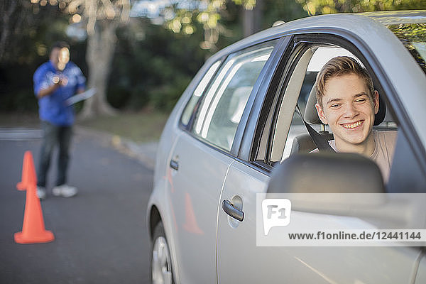 Smiling learner driver learning to drive looking at wing mirror of a car