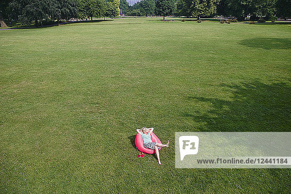 Relaxed woman sitting in inflatable seat on meadow