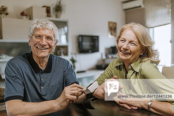Smiling senior couple with blood pressure gauge