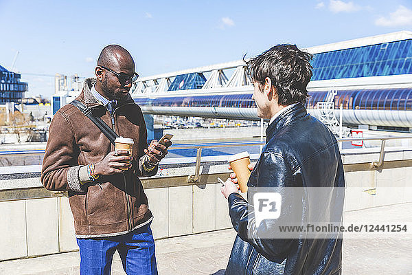 Russia  Moscow  two businessmen with coffee to go and smartphone in the city