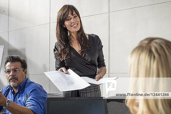 Smiling businesswoman handing over paper on a meeting in conference room