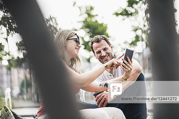 Happy couple sitting on a bench sharing cell phone
