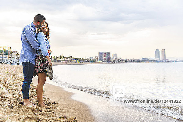 Spain  Barcelona  couple standing barefoot on the beach